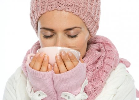 Woman in knit scarf, hat and mittens drinking hot beverage