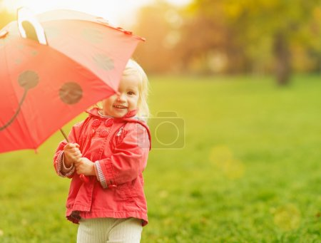 Photo for Smiling baby looking out from red umbrella - Royalty Free Image