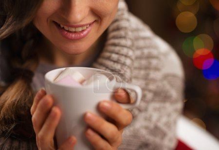 Closeup on hot chocolate with marshmallows in hand of happy girl