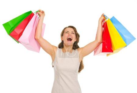 Photo pour Joyeux jeune femme avec des sacs à provisions réjouissant le succès - image libre de droit