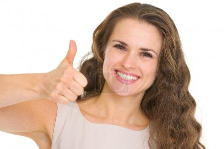 Photo pour Portrait de jeune femme souriante en robe montrant pouces vers le haut - image libre de droit