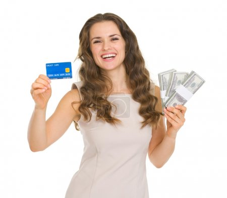 Photo for Happy young woman holding credit card and dollars packs - Royalty Free Image