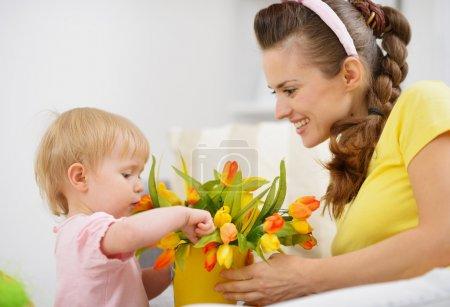Photo pour Heureuse mère et bébé, faire la décoration avec bouquet de tulipes en seau - image libre de droit