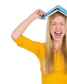 jeune fille étudiante en colère avec livre sur tête