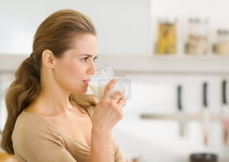 Young woman drinking milk in modern kitchen