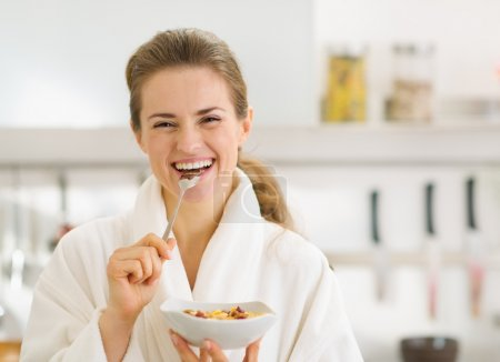 Photo for Smiling young woman in bathrobe eating healthy breakfast - Royalty Free Image