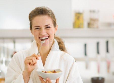 Lächelnde junge Frau im Bademantel isst gesundes Frühstück