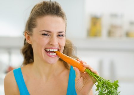 Photo for Happy young woman eating carrot in kitchen - Royalty Free Image
