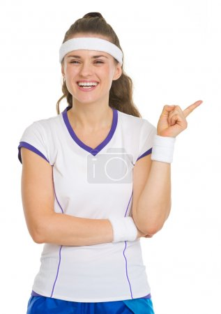 Happy tennis player pointing on copy space