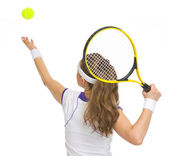 Tennis player serving ball. rear view
