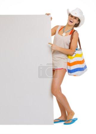Photo pour Portrait pleine longueur de souriante jeune femme de plage en chapeau pointant sur panneau d'affichage vierge - image libre de droit