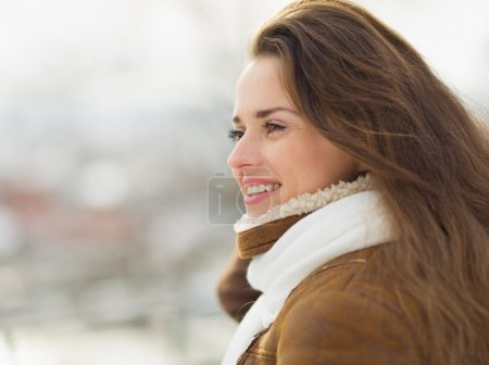Portrait of happy young woman looking on copy space in winter ou