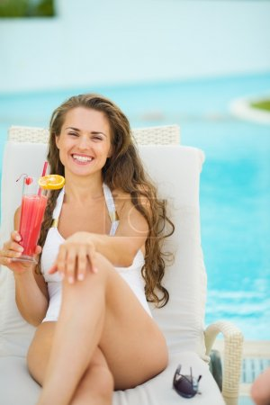Photo for Portrait of smiling young woman laying on sunbed and enjoying cocktail - Royalty Free Image