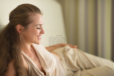 Smiling young woman laying on sofa