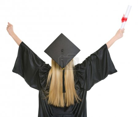 Woman in graduation gown rejoicing success . rear view