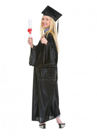 Photo for Full length portrait of young woman in graduation gown showing diploma and thumbs up - Royalty Free Image