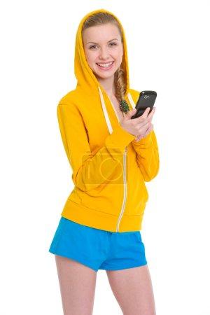 Smiling teenager girl writing sms
