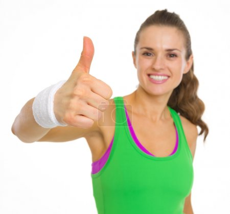 Photo for Closeup on fitness young woman showing thumbs up - Royalty Free Image