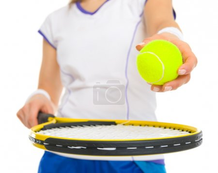 Closeup on female tennis player with racket and ball