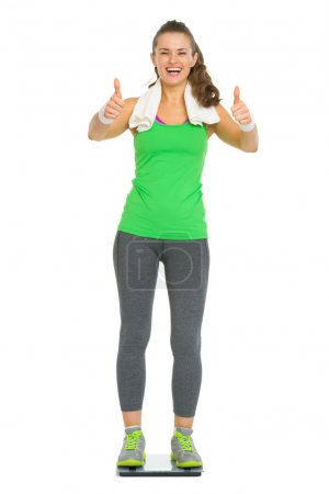 Happy fitness young woman standing on scales and showing thumbs