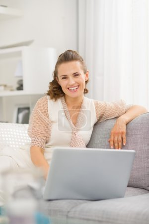 Photo for Smiling young woman sitting on sofa in living room with laptop - Royalty Free Image