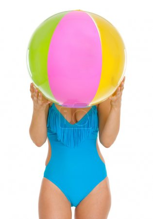 Young woman in swimsuit hiding behind beach ball