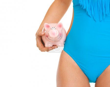 Closeup on piggy bank in hand of woman in swimsuit