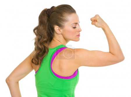 Fitness young woman showing biceps