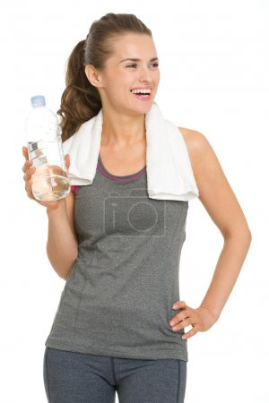 Smiling fitness young woman with bottle of water looking on copy