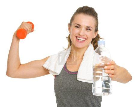 Photo pour Happy fitness jeune femme tenant des haltères et donnant bouteille d'eau - image libre de droit