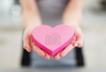 Photo pour Gros plan sur le cœur en main de la jeune femme - image libre de droit