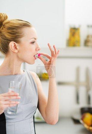 Photo pour Jeune femme manger pilule dans la cuisine - image libre de droit