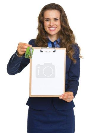 Happy realtor woman with keys showing blank clipboard