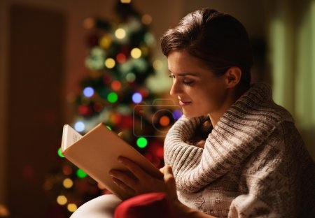 Happy young woman reading book in front of christmas tree