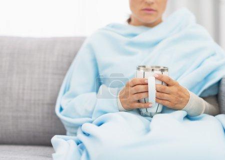Photo pour Gros plan sur la tasse avec boisson chaude dans la main de la femme malade - image libre de droit