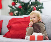 Happy baby in christmas costume eating cookie