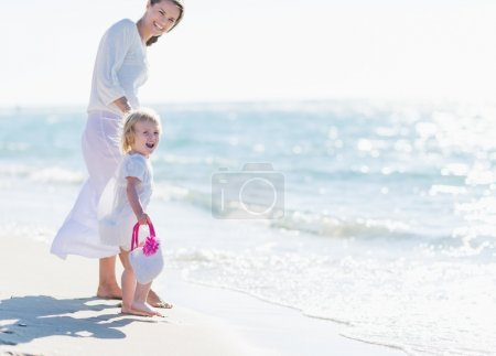 Happy mother and baby on sea shore