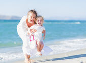 Happy mother and baby on sea shore having fun