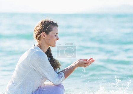 Young woman taking handful of water
