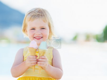 Smiling baby eating two ice cream horns