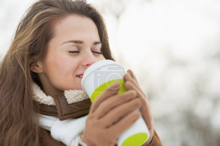 Happy young woman holding cup of hot beverage in winter outdoors