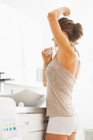 Woman applying roller deodorant