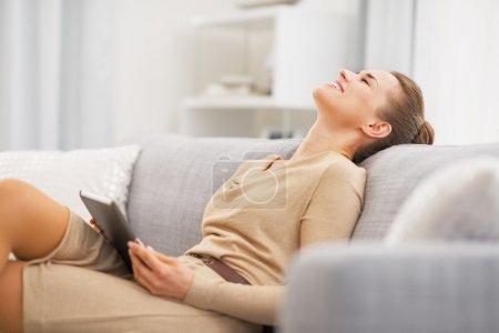 Photo pour Jeune femme détendue assise sur un canapé avec tablette pc - image libre de droit