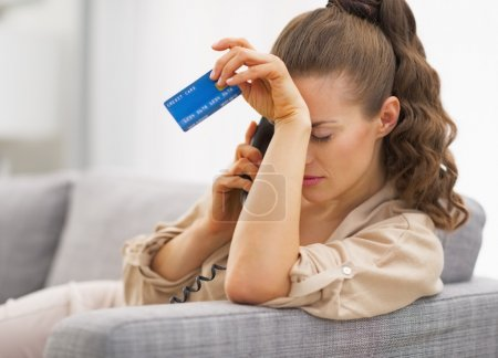 Photo for Frustrated young woman with credit card and talking phone - Royalty Free Image