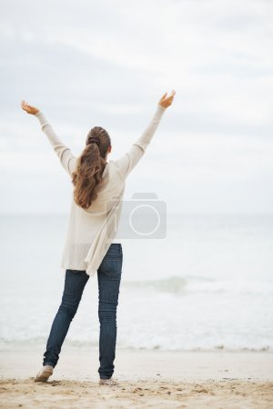 Woman in sweater on lonely beach