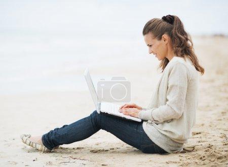 Photo pour Jeune femme en pull assis sur une plage solitaire et utilisant un ordinateur portable - image libre de droit