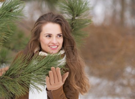 Happy young woman near fir-tree looking on copy space