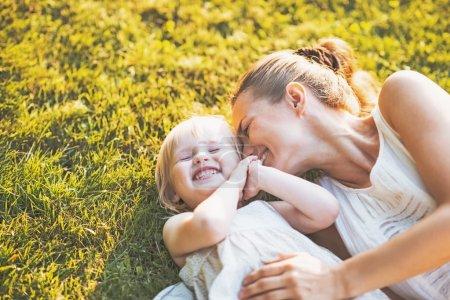 Photo pour Heureuse mère et le bébé couché sur le pré - image libre de droit