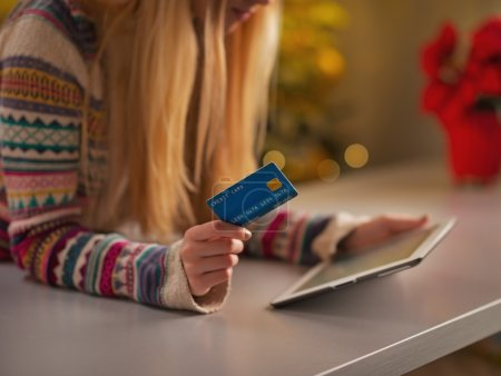 Teenage girl with credit card using tablet pc in christmas decorated kitchen