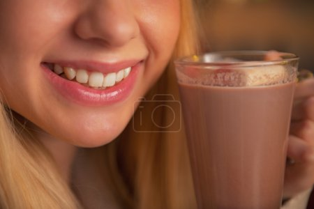 Closeup on teenage girl drinking cup of hot chocolate